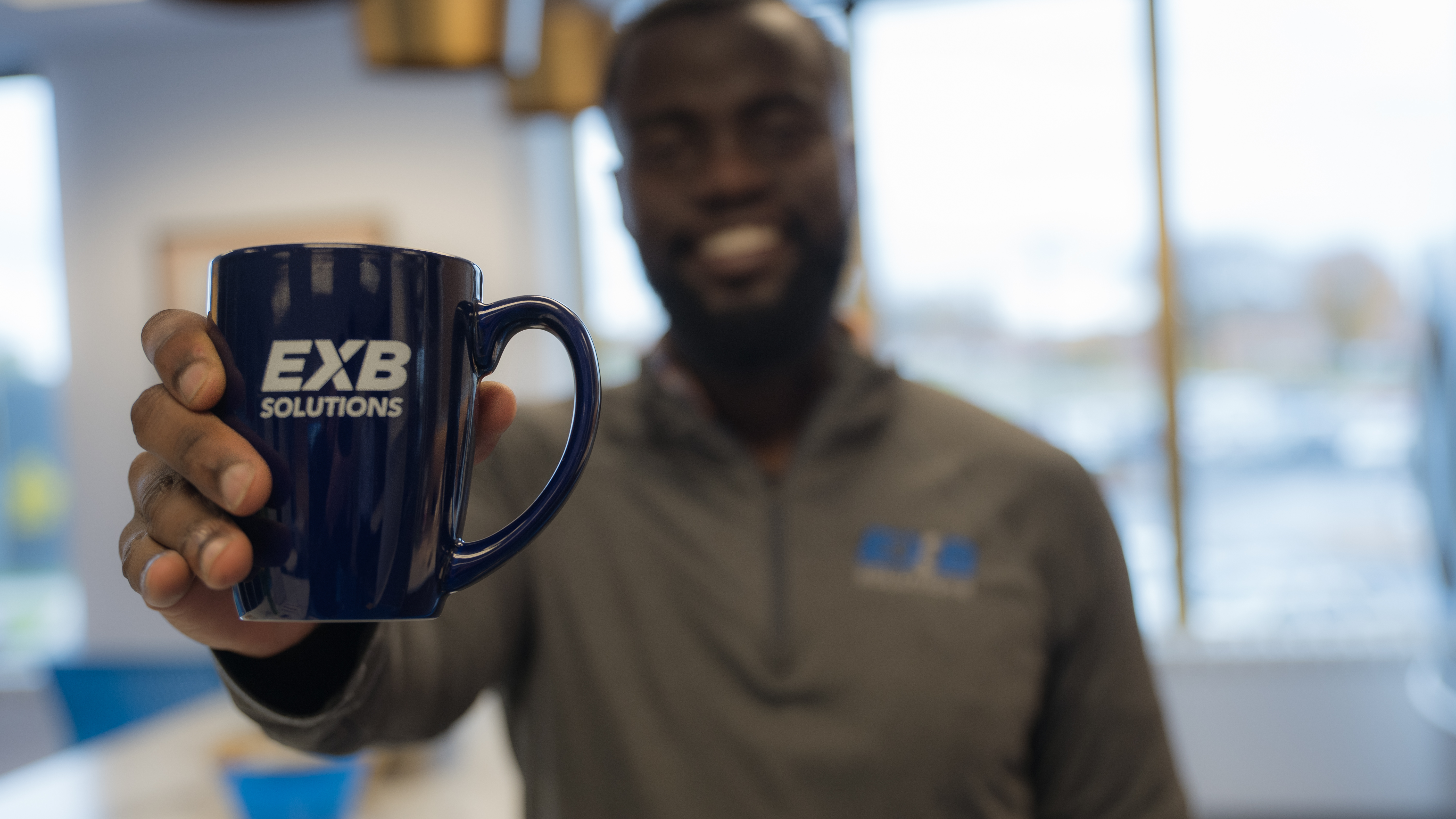 Team member holding EXB coffee cup