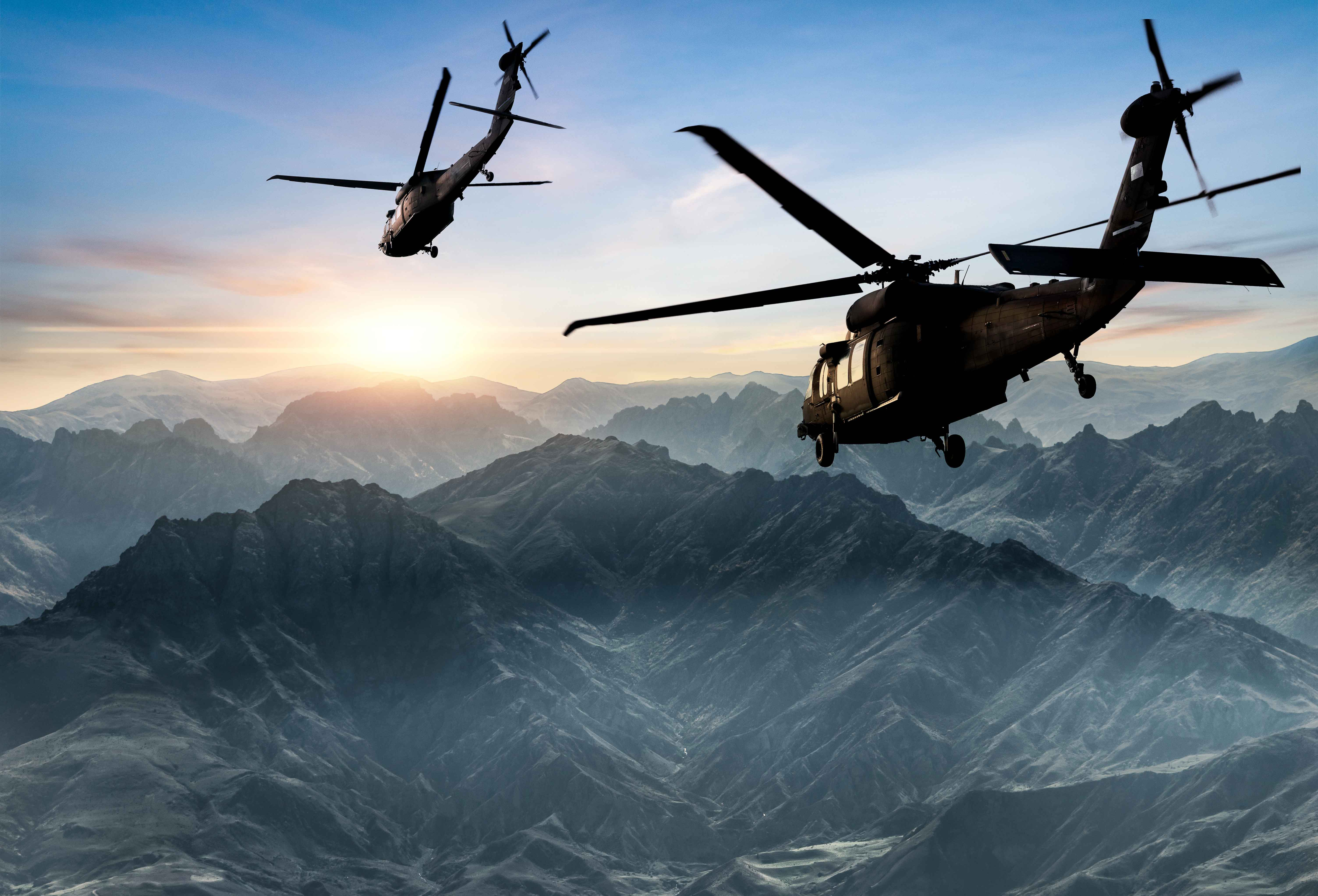 Helicopters flying over mountains